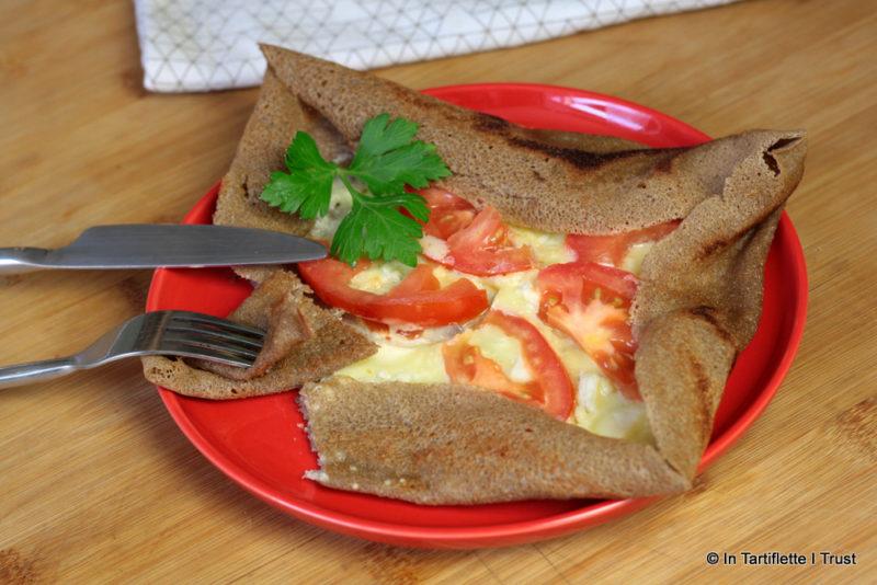 Galette de blé noir à la crème, chèvre, emmental et tomates